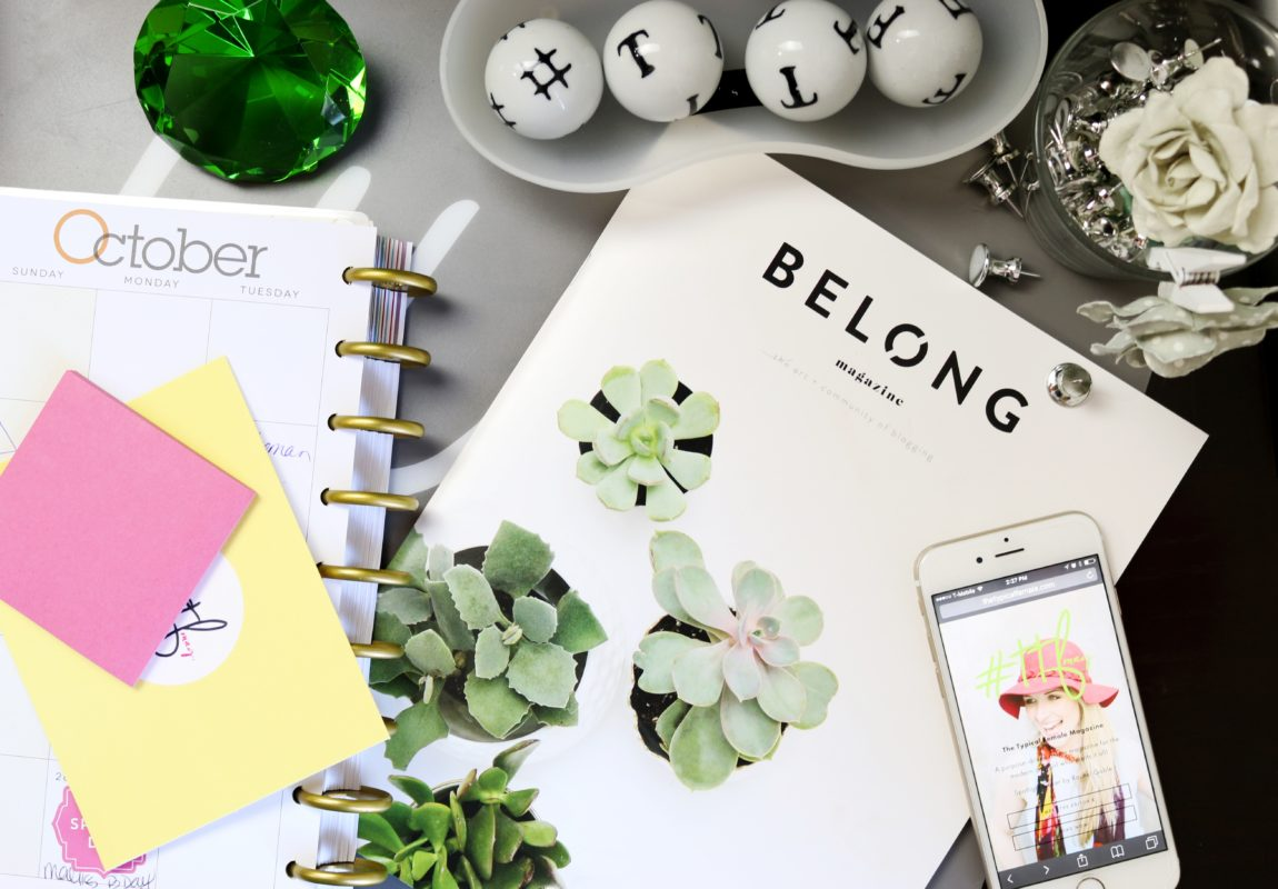 Planner, iPhone, magazine, plants, and desk accessories on top of table