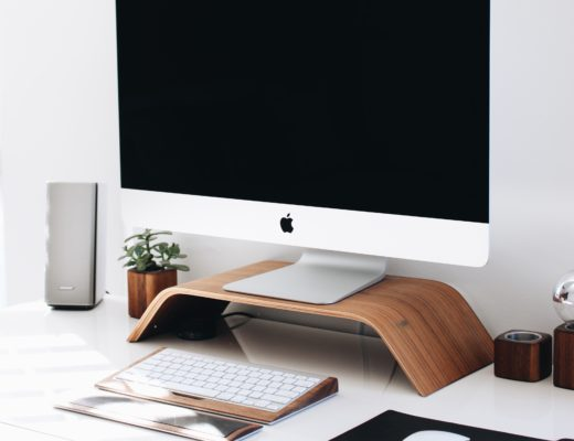 Mac computer with keyboard, mouse, and desk accessories on top of white desk