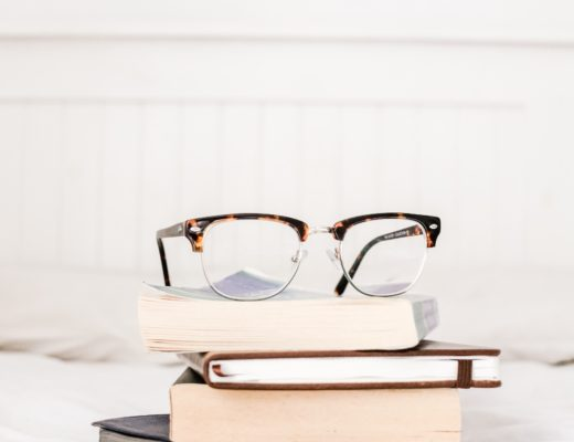 Stack of books on bed with glasses sitting on top