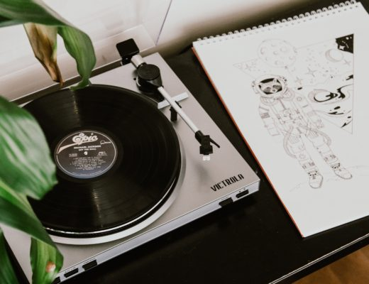 Record player on table next to a drawing