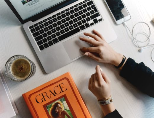 Women's hands on laptop next to iPhone, earbuds, cup, and book