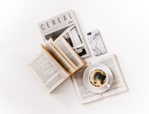 Book, magazine, iPhone, and cup of coffee on white desk