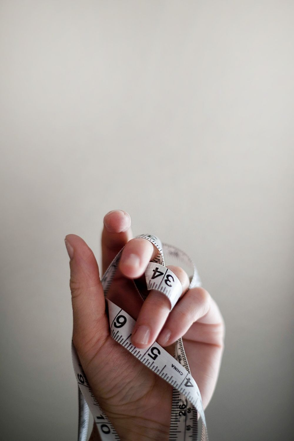 Measuring tape wrapped around hand