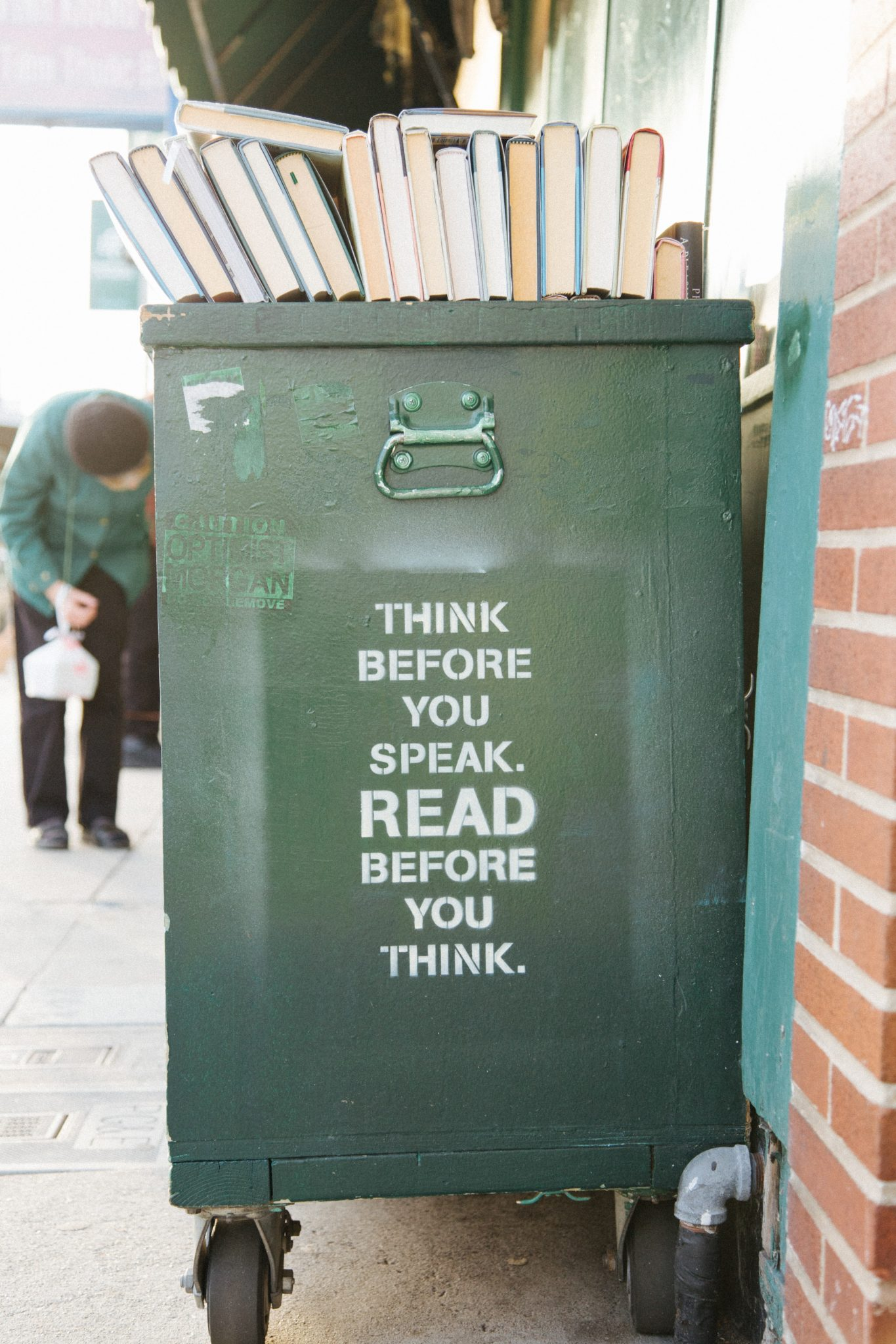 Outside bookshelf with sign that says think before you speak, read before you think