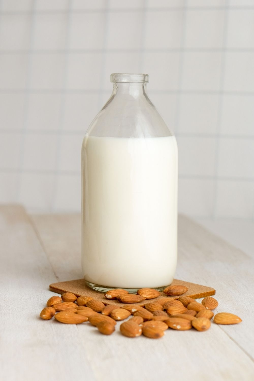 Glass milk jar with almonds in front on top of a table