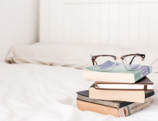 White bed with stack of books with glasses sitting on top
