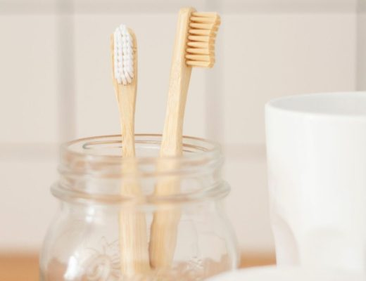 Two bamboo toothbrushes in mason jar