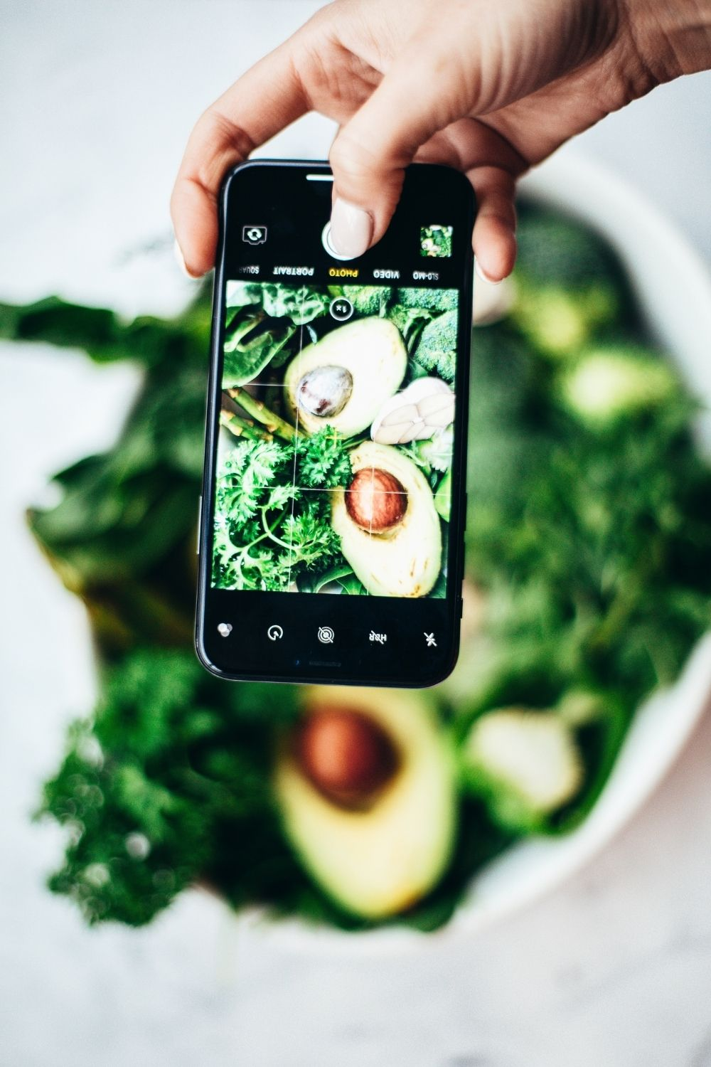Person taking picture of a bowl of vegetables