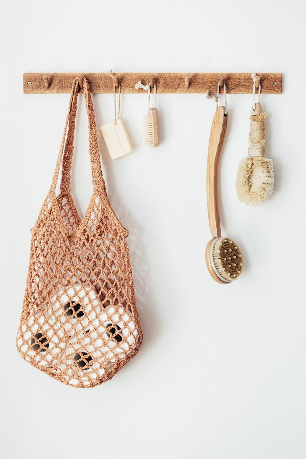 Mesh bag with toilet paper, body brushes and eco-friendly toiletries on wooden hanger