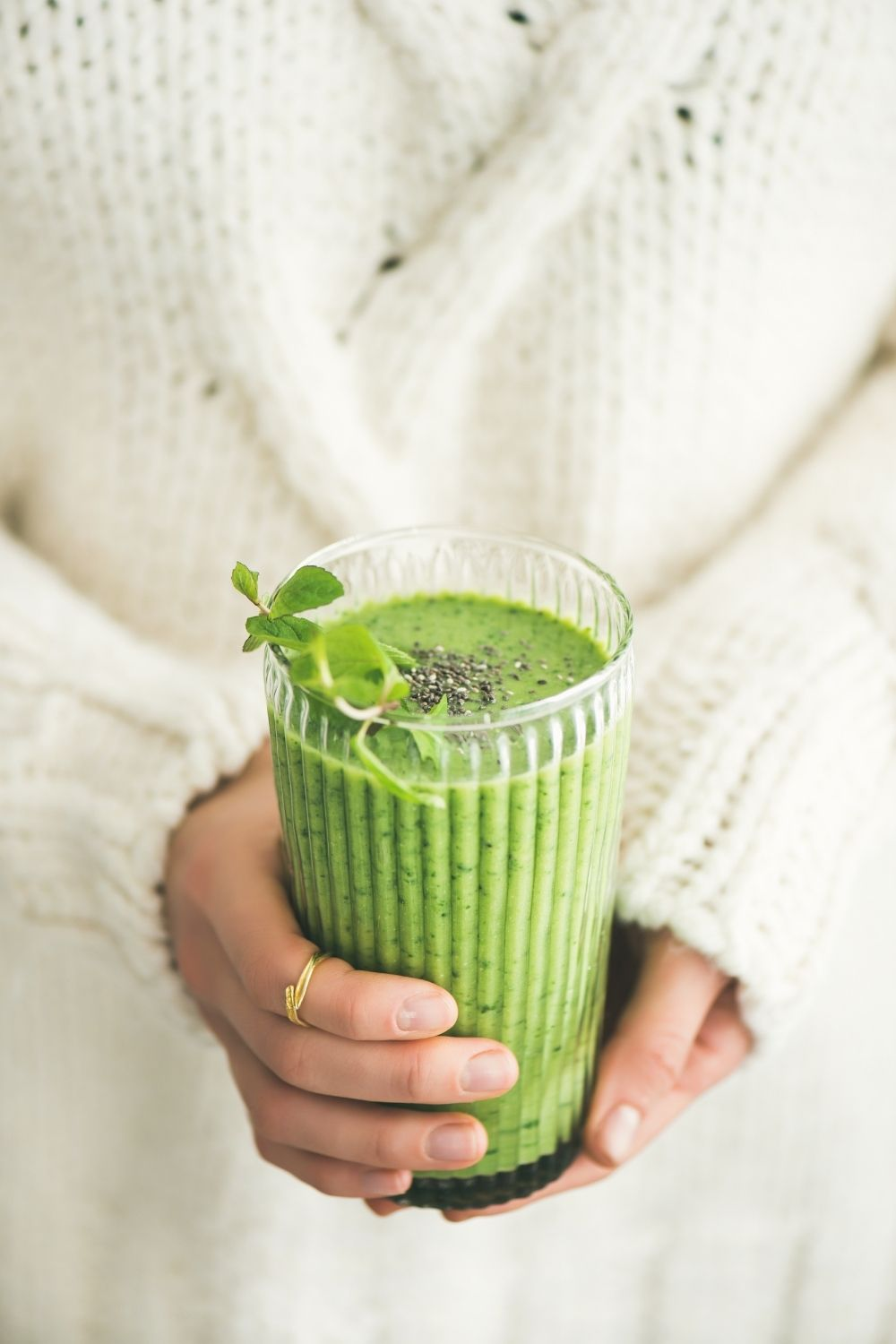 Woman in white sweater holding a glass of green juice