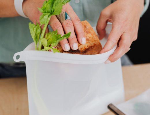 Person putting a sandwich into a reusable silicone bag