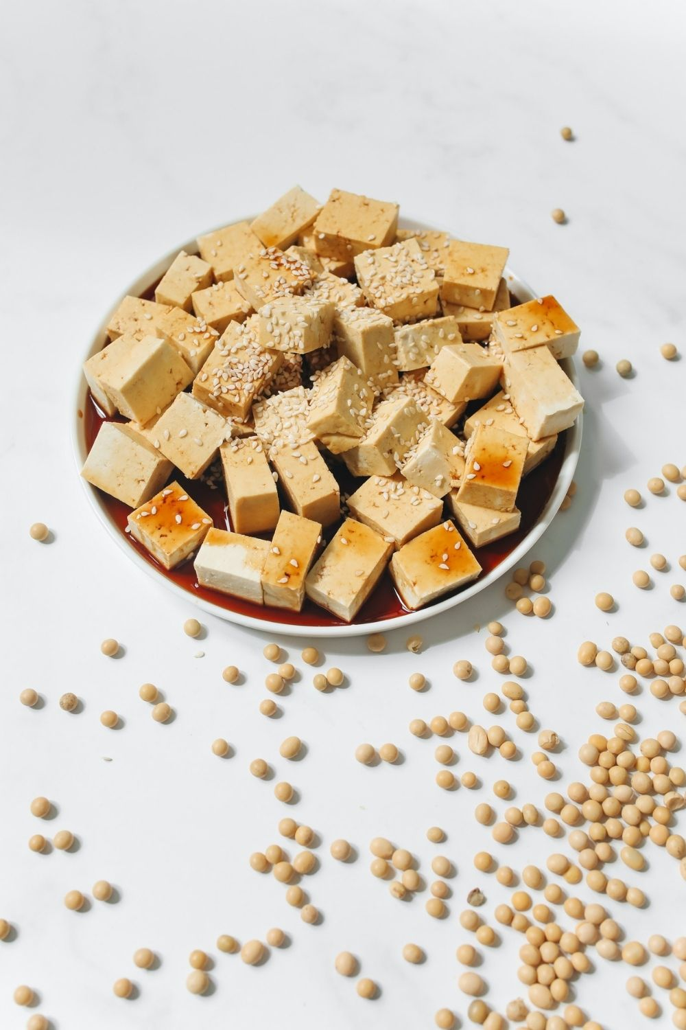 Tofu in bowl next to soybeans on white table