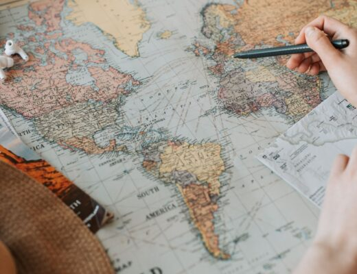 Person tracing world map on a table